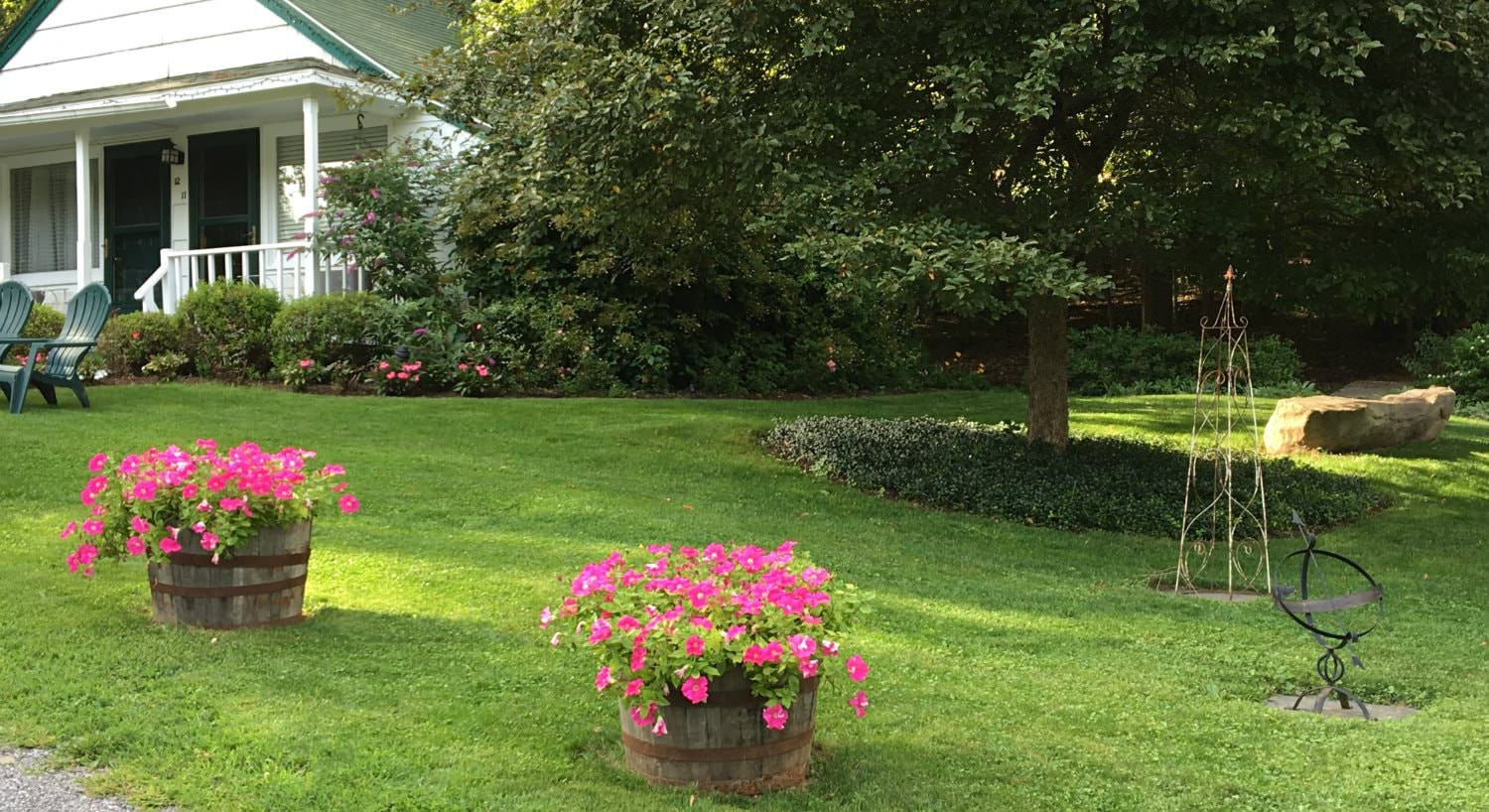 Green grassy lawn with wood buckets of pink flowers, a large greeen tree and a white cottage in the background