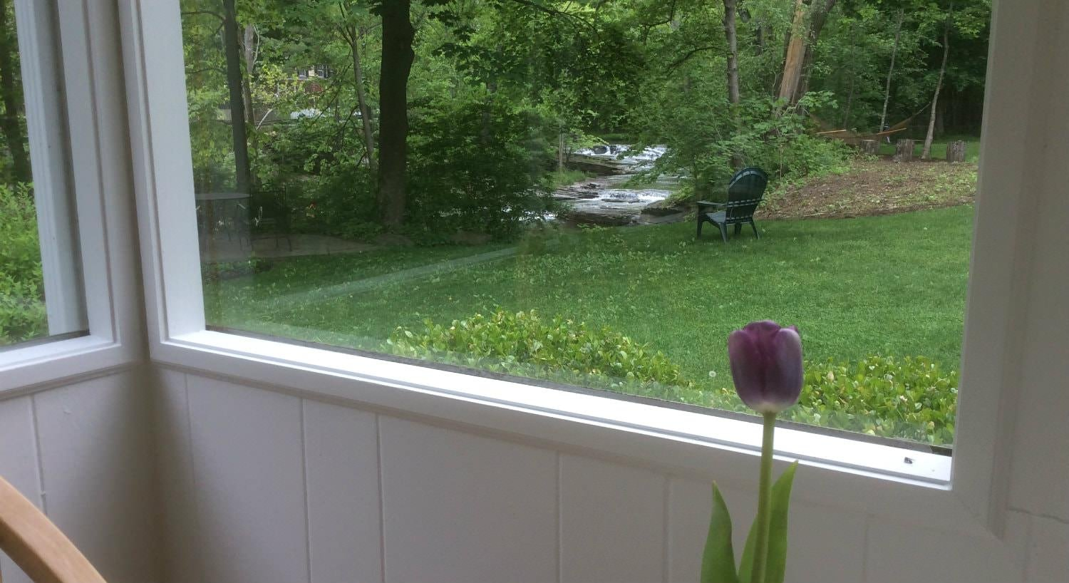 View through the window of a grassy lawn, a rippling stream, and lots of green trees
