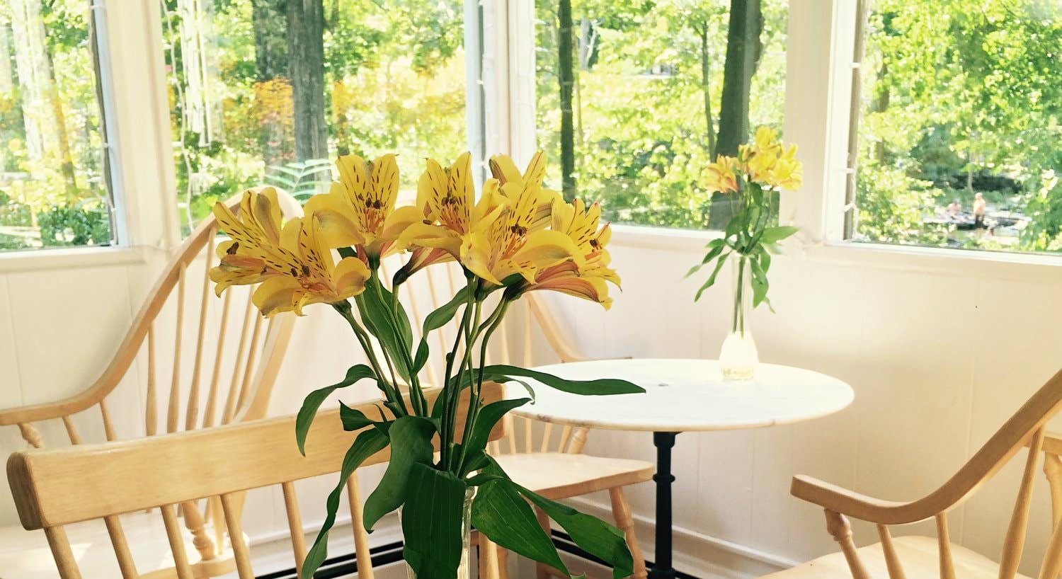 Small wood dining tables topped with vases of yellow lilies surrounded by windows with view of lush greenery