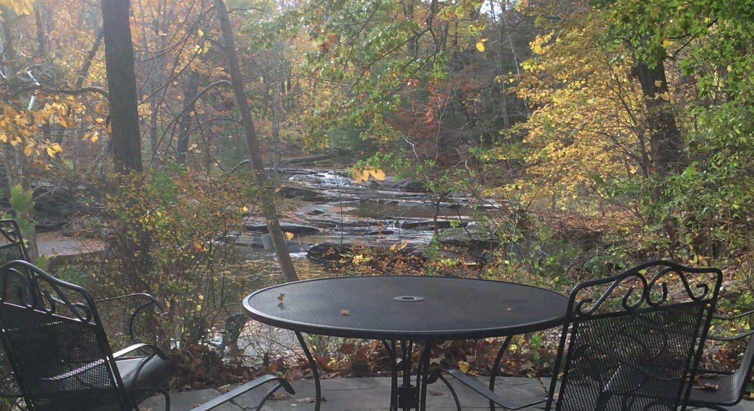 Black round metal table and chairs on a patio overlooking a stream and the woods with trees changing colors