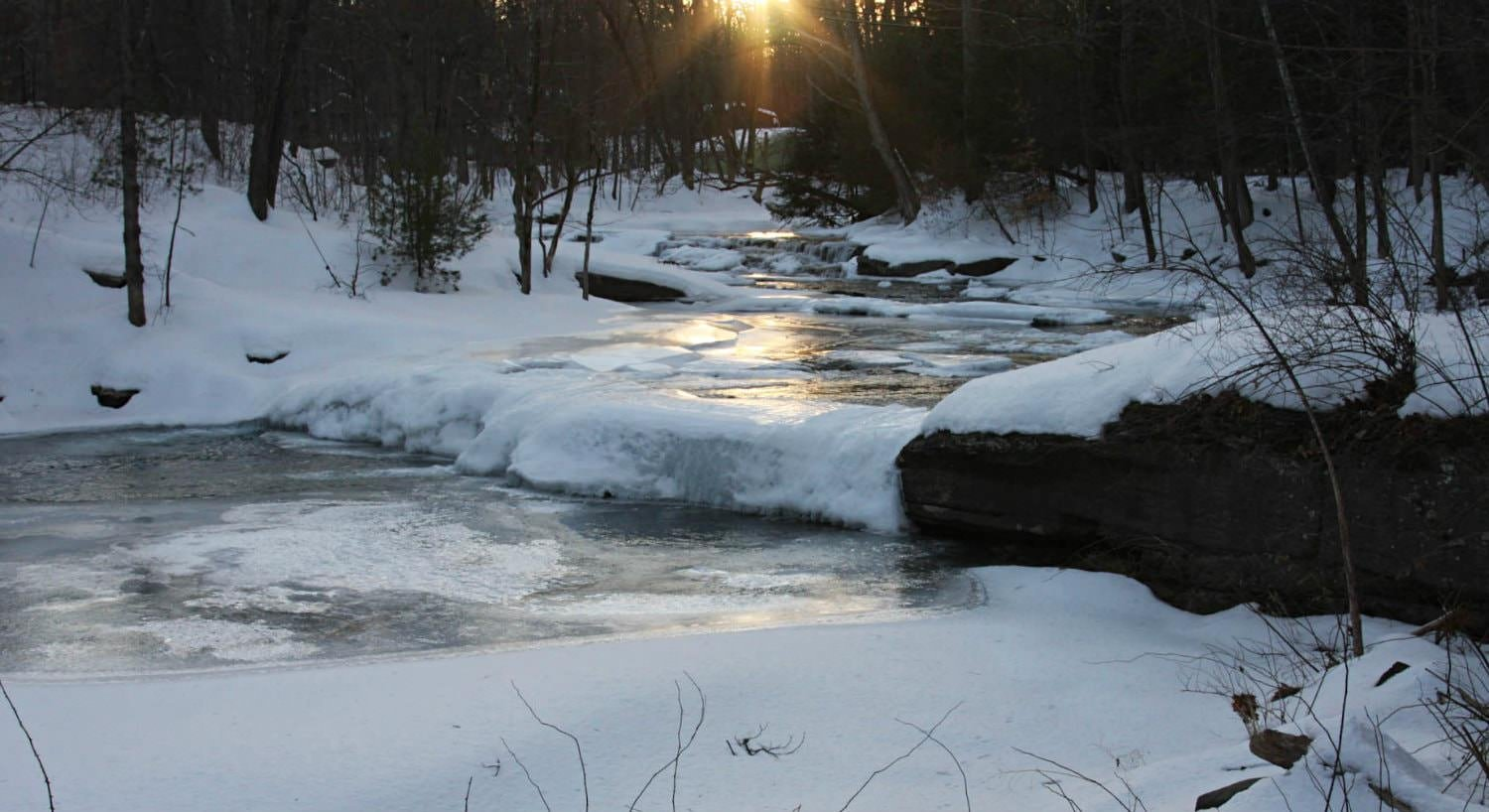 White snow and ice covered stream and woods with a golden setting sun in the distance