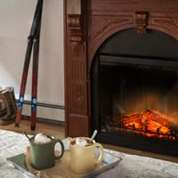 two mugs of hot cocoa on a tray on a bed with a fireplace in thw background with orange flats and a pair of cross country skis leaning against a white wall.