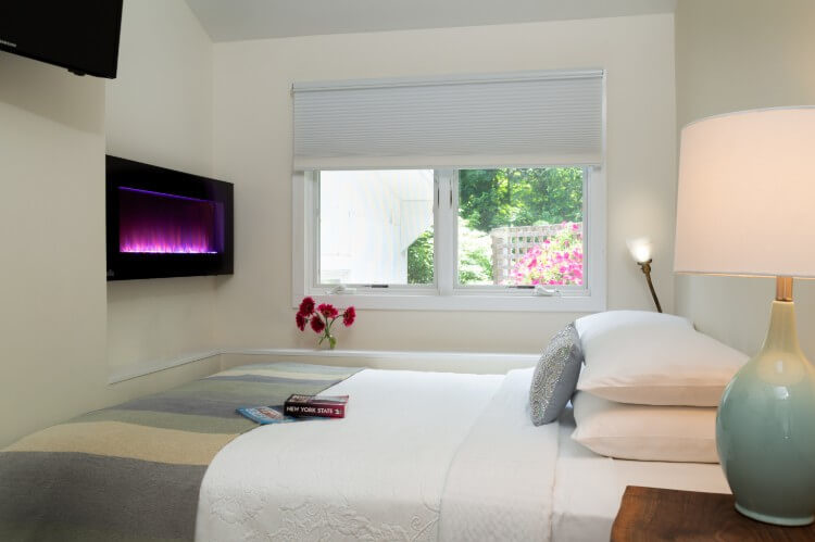 A bed with pillows, a window looking out over green trees and pink flowers, and an electric fireplace on the wall.
