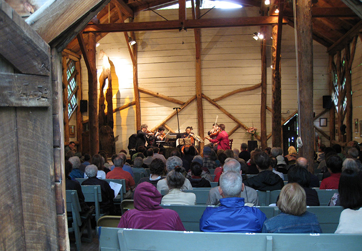 wooden building that is a concert hall, with musicians playing and audience backs