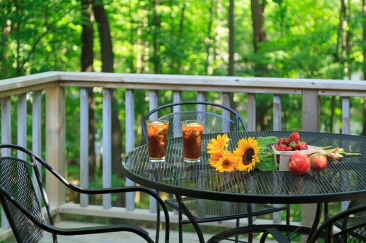 A patio table outdoors with flowers, drinks and fresh fruit.