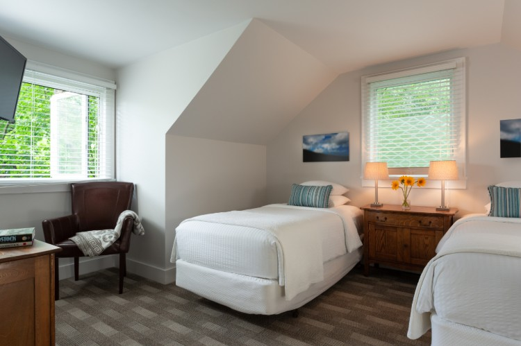 Brown carpet, a twin bed under a dormer ceiling and another twin in the corner. Theres a dresser between the beds and a chair by the window.