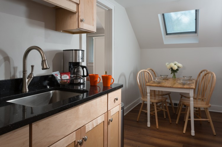 A black kitchen counter, coffee pot and dining table are part of the kitchen.