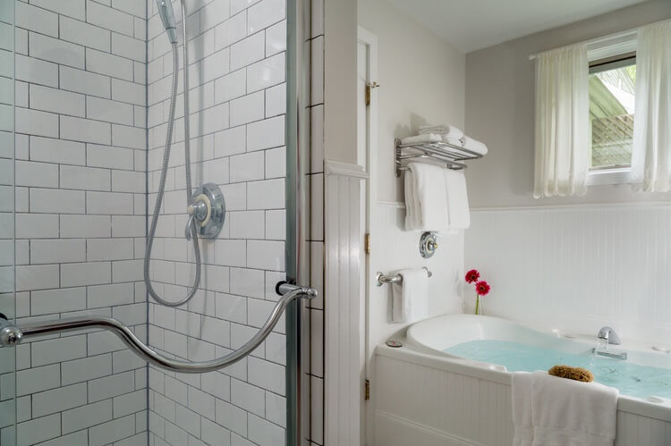 A shower with glass doors is on the left and a soaking tub with warm blue water is to the right. Everything in white tiles.