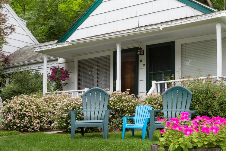 Three Adirondack chairs on green grass, in front of a small cottage with two doors.