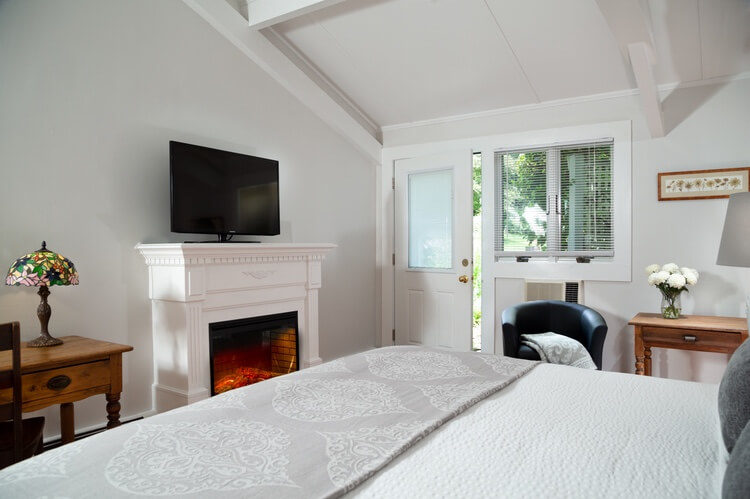 Gray room with white fireplace, lit and television on top of the mantle. Big bed is in the front part of the picture