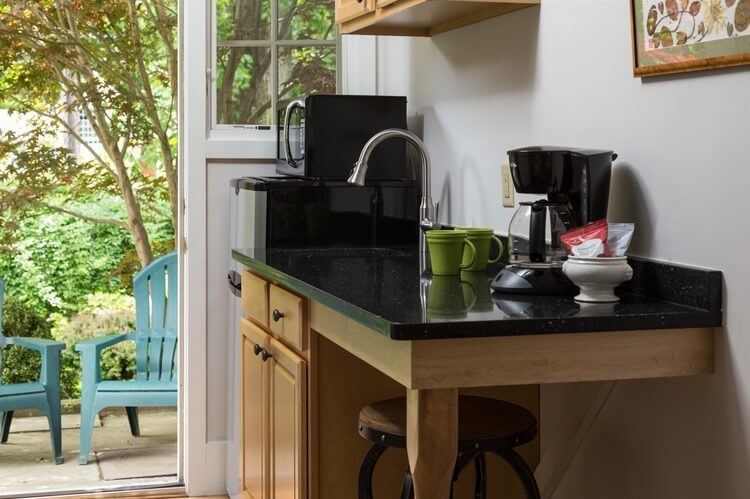 A black counter with sink and coffee pot, and brown cabinets are next to a window and a door the leads outdoors..