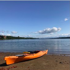 An orange kayak sits on brown sand, by blue water with a few whoite clouds in the sky.