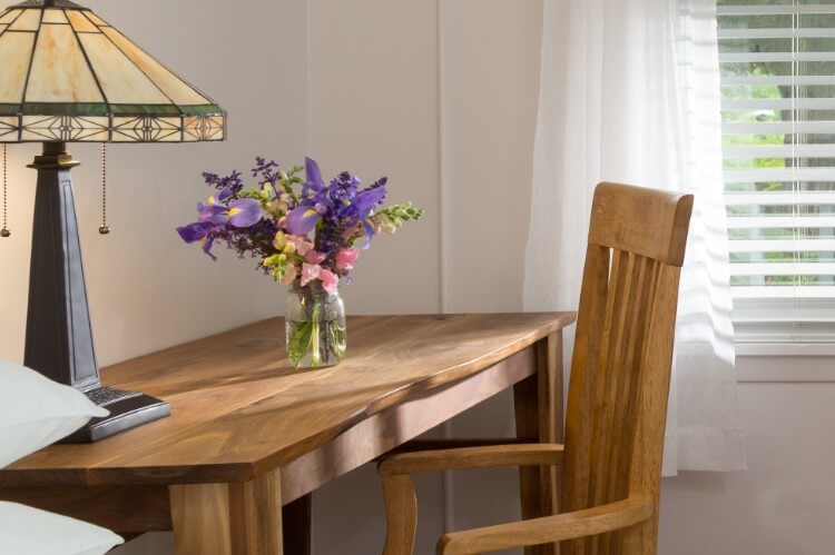 Sun streaming through window with purple flowers in a vase on a wooden desk.