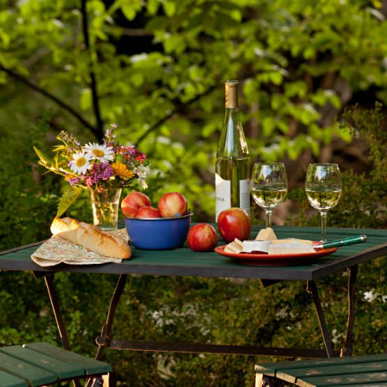 Slatted, outdoor table topped with wine bottle and glasses, apples in blue bowl, French bread, and vase of fresh wildflowers