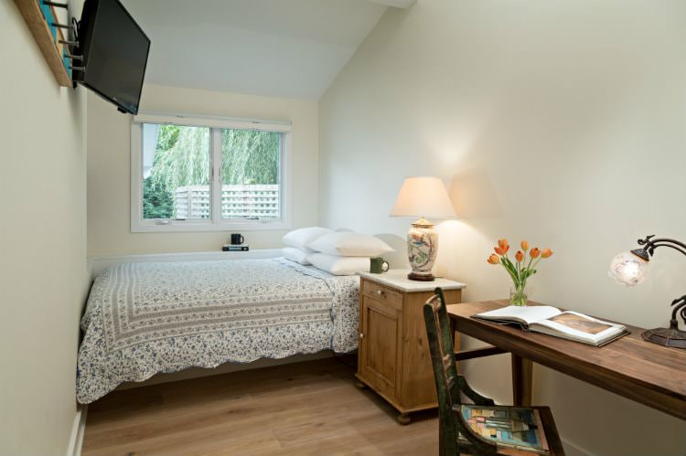 Beige vaulted room with wood floor, double window, floral quilt covered bed, nightstand with floral lamp, and desk with chair