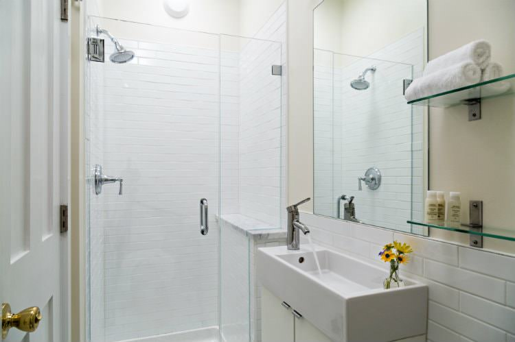 Beige and white bathroom, white tiled shower with glass door, glass shelves and white towels