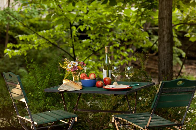 Green table and chairs topped with fresh flowers and apples, French bread, white wine, surrounded by lush greenery