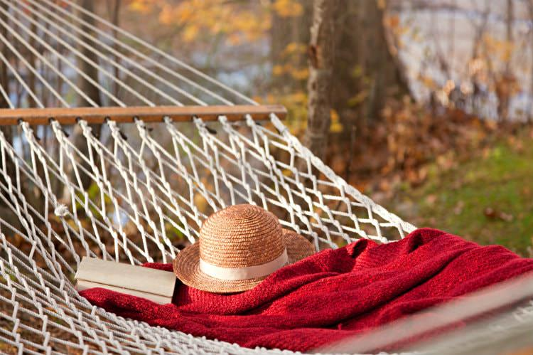 White netted hammock topped with straw hat, red blanket and book surrounded by autumn trees
