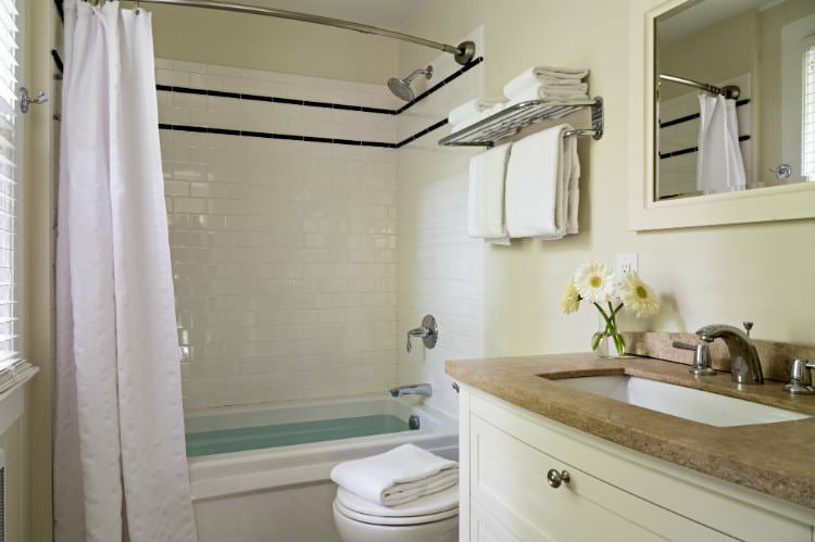 Beige and white bathroom with window, white towels, tan countertop, and curved shower rod with white curtain
