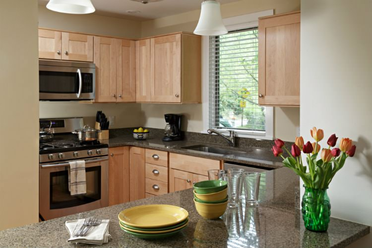Beige kitchen with natural cabinetry, stainless steel appliances, window over the sink and granite tops