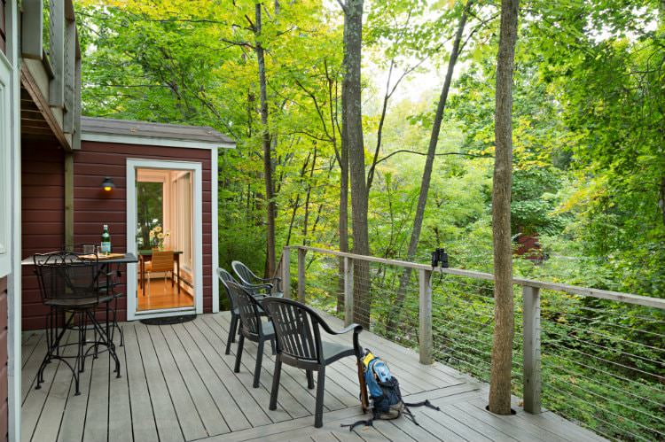 Spacious raised deck with small dining table for two and four chairs overlooking the wooded lush green view