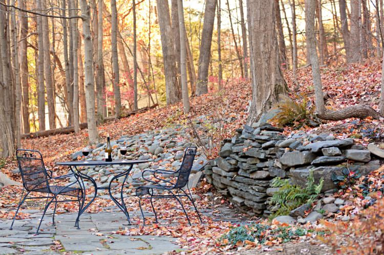 Black table and two chairs on a patio surrounded by woods, almost bare trees, and fallen leaves on the ground