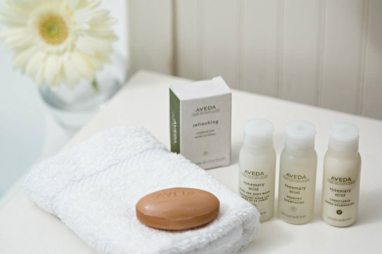 Bar of Aveda soap on white folded towel, Aveda soap box and Aveda sample size toiletries on white counter