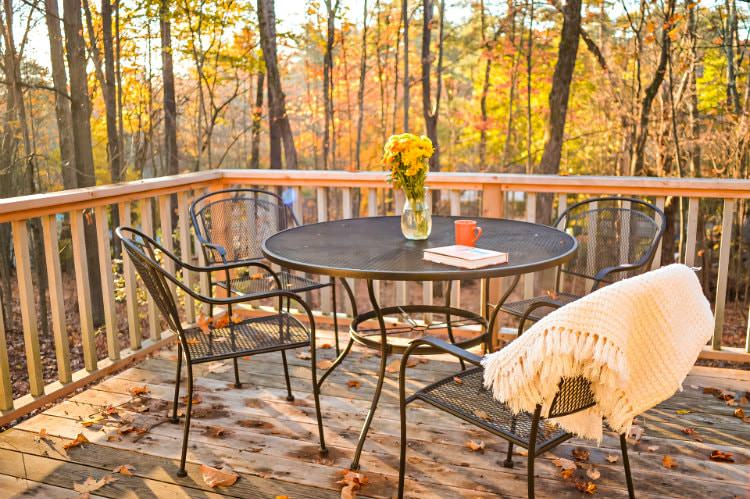 Wood deck with black metal table and chairs topped with fresh flowers, mug, book, and throw, overlooking woods