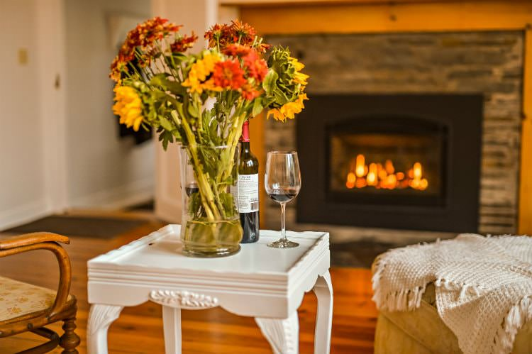Close up of small white end table topped with fresh flowers and wine, and view of lit fireplace in background