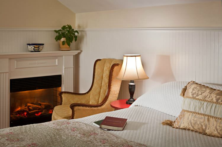 White covered bed with floral quilt, nightstand with lit lamp, and upholstered chair near a glowing fireplace