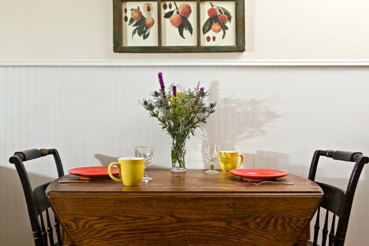 Wood drop-leaf table with two chairs, set for a meal and topped with fresh wildflowers