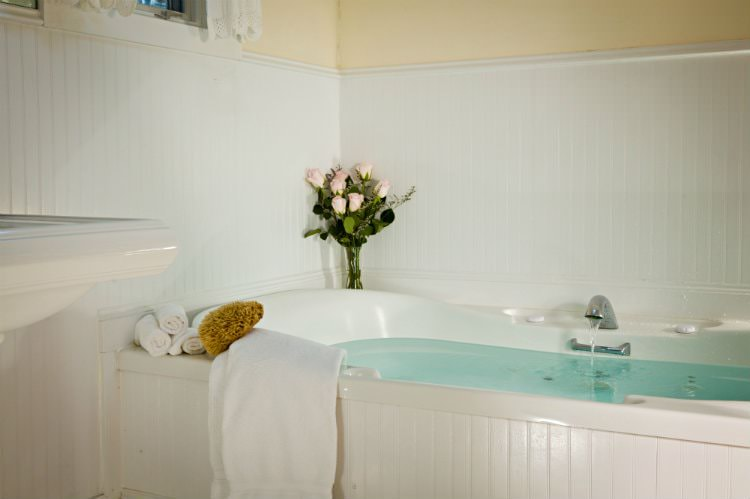 Cream bathroom with white beadboard, pedestal sink and soaker tub full of water with white towels and fresh flowers nearby
