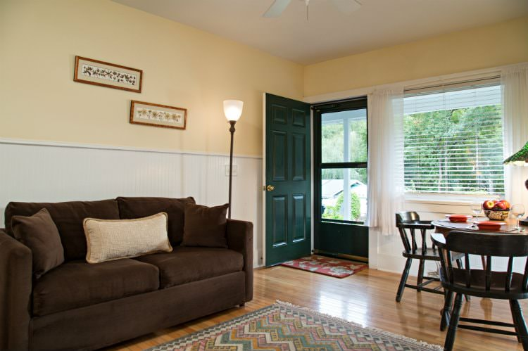Beige room with white beadboard, wood floors, brown upholstered couch and wood dining table and chairs