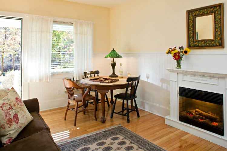 Beige room with white beadboard, lots of natural light, hardwood floors, glowing fireplace, and round wood dining table and chairs