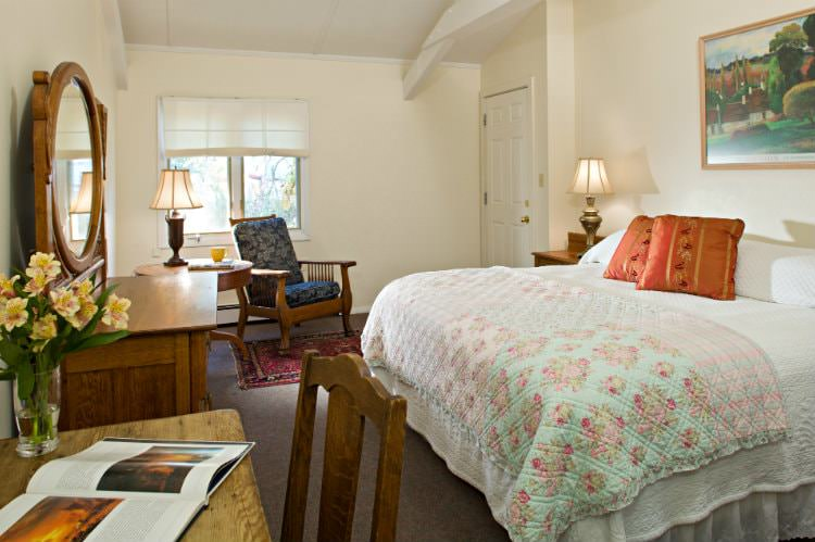 Beige room with quilt covered bed, sitting chair and end table near double window, and wood dresser with mirror