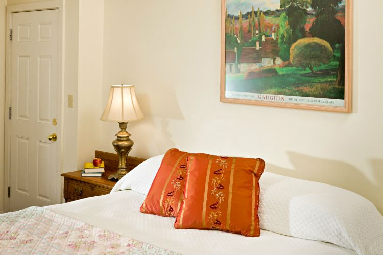 Beige room with white covered bed with floral quilt at the end, and wood nightstand with antique brass lamp