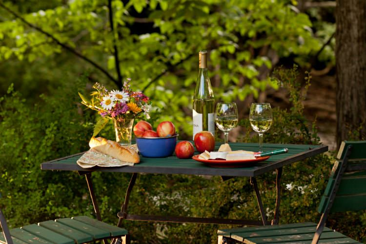 Green table topped with fresh flowers, white wine, red apples, French bread, surrounded by lush green woods