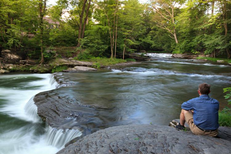 Man sitting on a rock ledge overlooking rippling stream with shallow waterfall surrounded by lush green woods