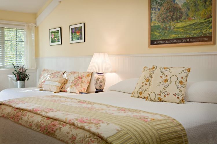 Beige vaulted room with white beadboard, white covered bed with floral quilt and lots of natural light