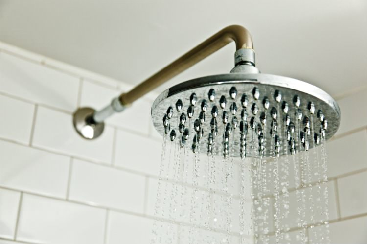 Close up view of rain shower head in white tiled shower
