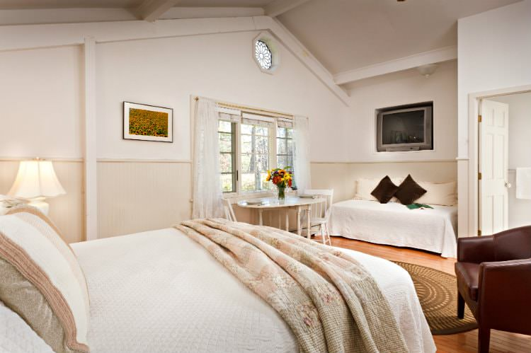White vaulted room with beige beadboard, hardwood floor, bed with white and floral quilts, flat screen tv and dining table