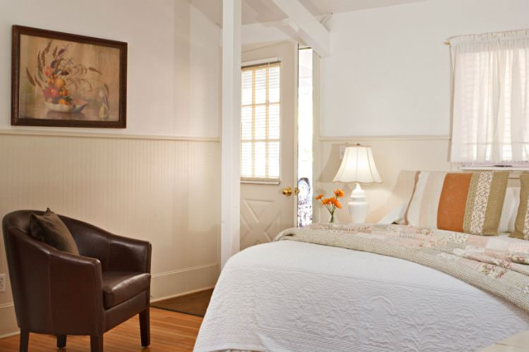 White room with beige beadboard, hardwood floor, bed with white and floral quilts, brown leather club chair, and natural light