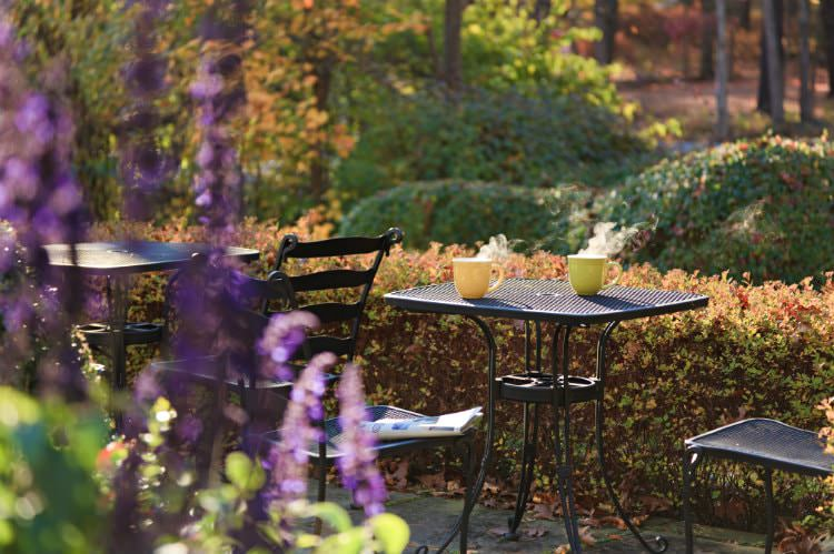 Black patio tables and chairs surrounded by shrubs, woods, and flowering plants