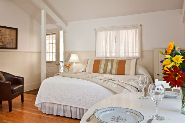 White room with beige beadboard, hardwood floor, bed with white and floral quilts, brown leather club chair and dining table