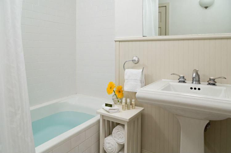 White bathroom with white tiled tub and shower, beige beadboard, white pedestal sink with mirror, and white towels