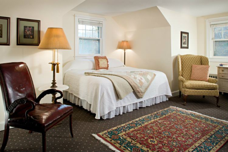 Beige room, large bed with white and floral quilts, carpeted floor with colorful rug, leather chair and upholstered chair