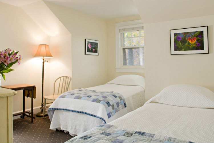 Beige room with window, two white and blue quilt covered beds, small drop-leaf table with chair and floor lamp