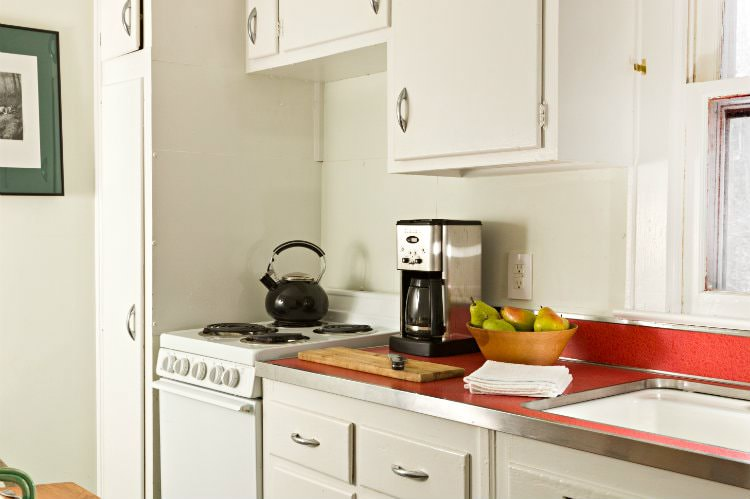White kitchenette with stove, red countertop with coffee maker, fresh pears and cutting board