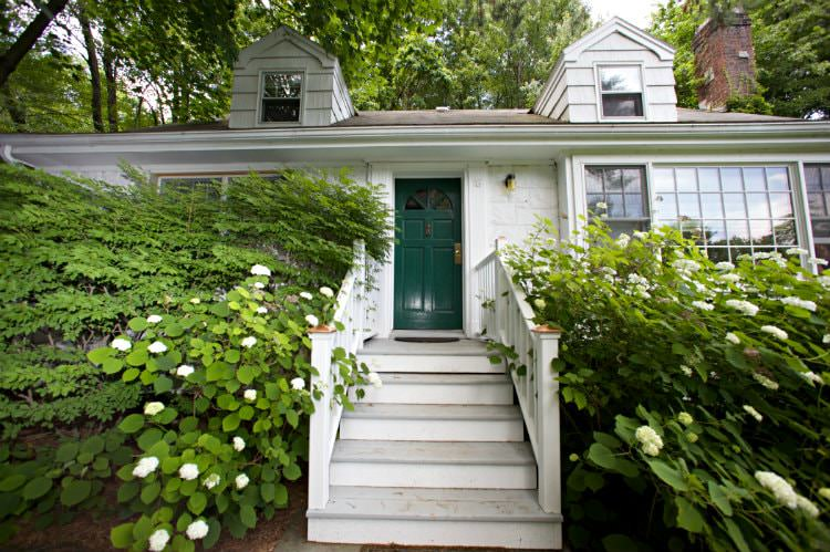 Exterior view of white cottage with green door, wood steps leading to the front door surrounded by green shrubs and trees