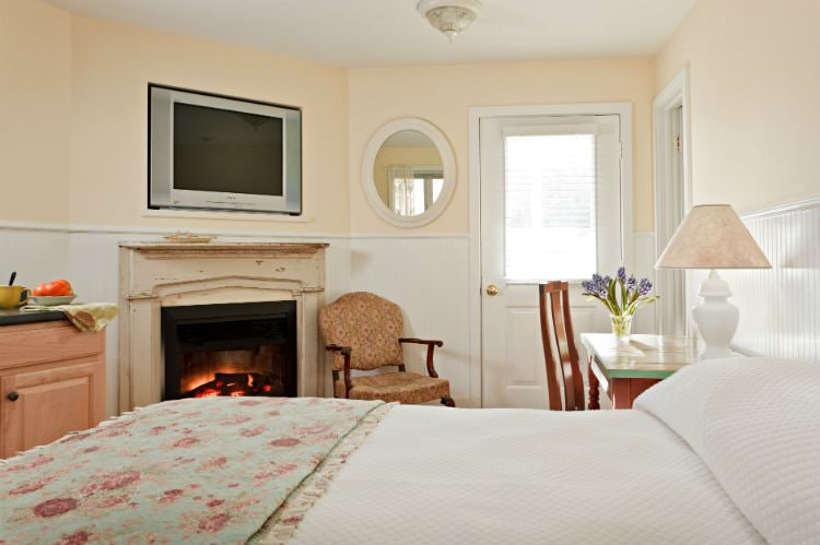 Beige room with white beadboard, bed with white and floral quilts, desk and chair, and fireplace with flat screen tv